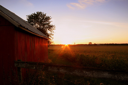 Picture of the Sun Setting Behind a Red Barn